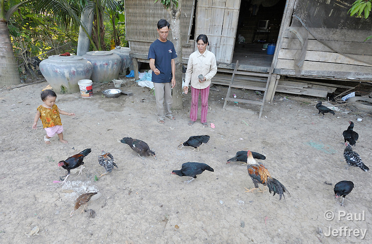 A couple feeds chickens outside their home in the Cambodian village of Bour.
