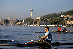 Single and two man shell with men rowing on Lake Union at sunrise with the Space Needle in the background, Seattle, Washington State USA