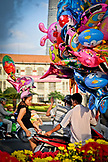 VIETNAM, Ho Chi Minh, Saigon, young woman getting a baloon from a street vendor, motorcycle in the back