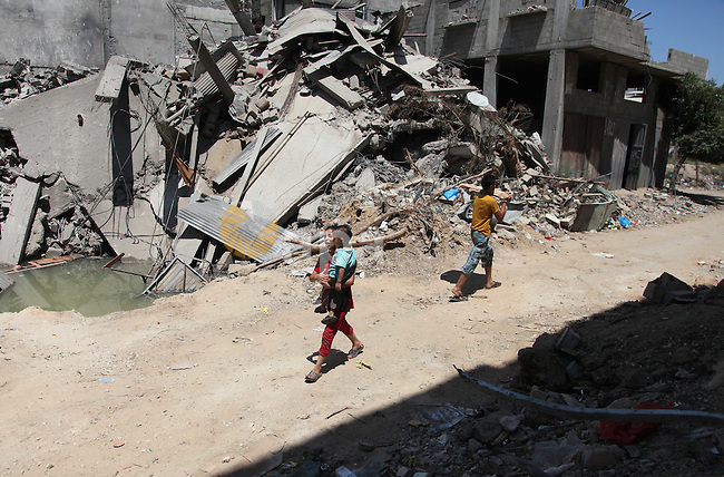 "Palestinian children walk past the debris of a destroyed house after it was hit by an Israeli military strike in Gaza city on August 10, 2014. A senior Hamas official said there was a ""weak"" possibility that Gaza truce talks would succeed and that Palestinian negotiators could leave Cairo after a meeting with Egyptian mediators. Photo by Ezz Zanoun"