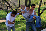 Palestinians carry an injured youth during clashes with Israeli settlers in the West Bank village of Yasuf south of Nablus, Friday, March 18, 2011. Photo by Wagdi Eshtayah