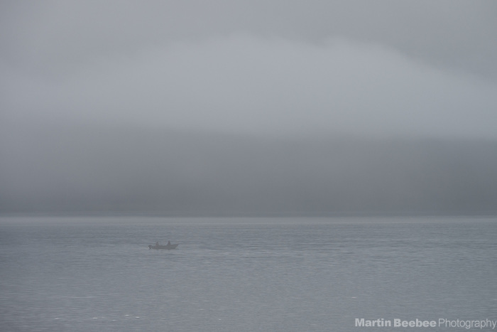 A couple fisherman head out in a boat on Resurrection Bay in thick fog, Seward, Alaska