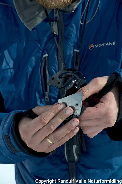 Mann skifter skjær på isbor. ---- Man reparing ice drill.