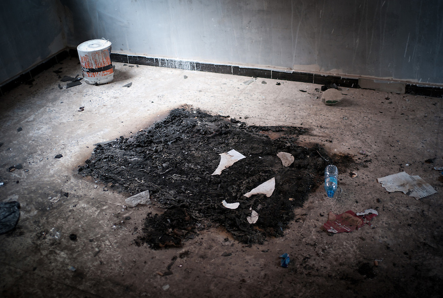 A burned pportrait of Gaddafi on the floor of the special police headquarters in Tobruk, LIbya.