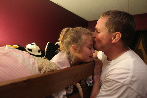 "Luke Jensen kisses his daughter, Libby, 8, goodnight at bedtime in their Colo home on June 9.  ""My family support has made all the difference in the world,"" Luke says of his coping with PTSD stemming from his deployment to Afghanistan in 2009."