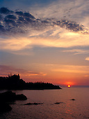 Sunrise behind US Coast Guard Station Marquette lighthouse in Marquette Michigan on Lake Superior.