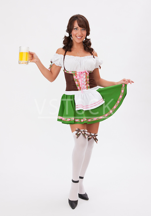 Young woman wearing Oktoberfest costume holding beer stein, studio shot