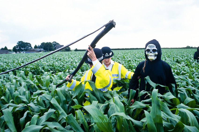 A demonstrator dressed as the GM Grim Reaper is arrested after cutting through a field of GM test maize  at an  Anti GM  protest in Bridport,  Dorset