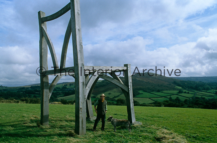Portrait of artist Henry Brudenell-Bruce with his dog under an enormous wooden chair that he built in the Devon countryside