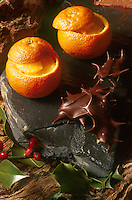 An orange dessert served on a piece of slate and decorated with chocolate-dipped holly leaves