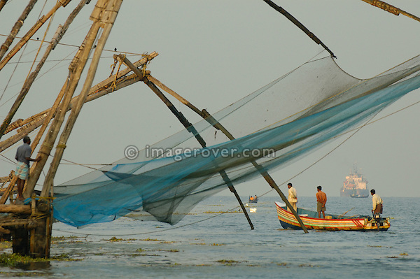 India, Kerala, Fort Cochin (Cochi, Kochi). Indian fishermen in their small boat and chinese style fishing net in Cochin harbour. No releases available.