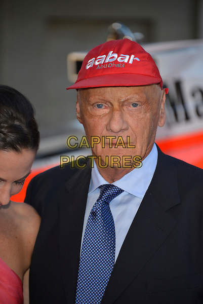 Niki Lauda<br /> 'Rush' world film premiere at the Odeon Leicester Square cinema, London, England.<br /> 2nd September 2013<br /> headshot portrait blue suit red baseball cap hat  <br /> CAP/PL<br /> &copy;Phil Loftus/Capital Pictures