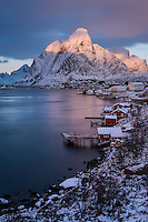 Dramatic winter sunrise on Olstind and Reine, Moskenesøy, Lofoten Islands, Norway