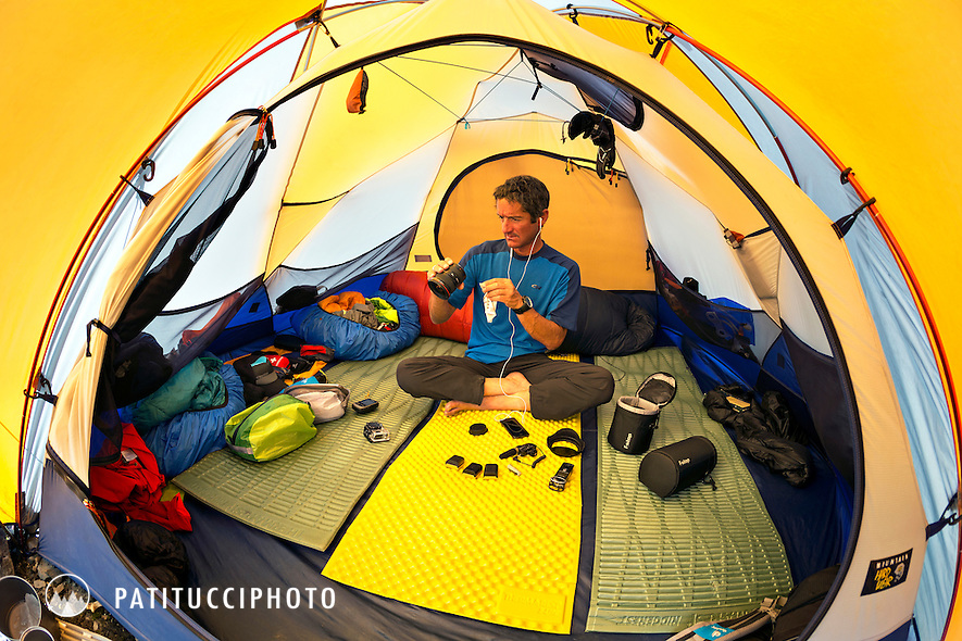 Photographer Dan Patitucci inside his tent at Annaurna Advance Basecamp cleaning camera gear while waiting for Ueli Steck during his historic solo ascent of the south face of the 8000 meter peak