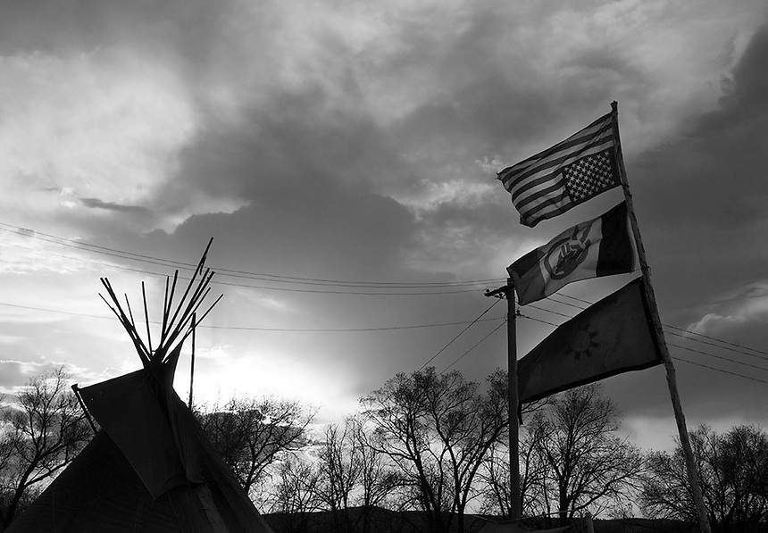 American flag upside down, the American Indian movement and Lakota flags waving at the Zero Tolerance camp. The young generation of Lakota warriors built the camp on the border with White Clay,Nebraska. The student lead movement declared- The myth of the drunken Indian is over. The town of White Clay has four houses and seven liquor stores. A significant part of Whiteclay's economy is based on alcohol sales to residents of the Pine Ridge Indian Reservation, located two miles north across the border in South Dakota, where alcohol consumption and possession is prohibited. According to the Nebraska Liquor Control Commission, beer sales at Whiteclay's four liquor stores totaled 4.9 million cans per year.