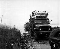 """Return of POW's during Operation """"Big Switch,"""" Panmunjom, Korea.  Communist POW's ripped off their clothing and strewed it along the road.  Some of the clothing is burning.  August 12, 1953. Larsen. (Navy)<br /> NARA FILE #:  080-G-626977<br /> WAR & CONFLICT BOOK #:  1498"""