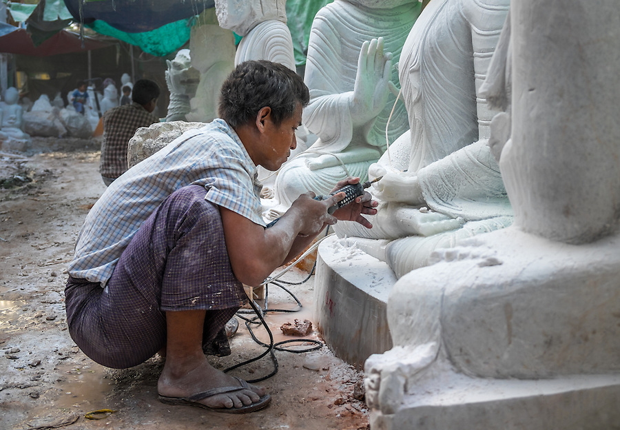 MANDALAY, MYANMAR - CIRCA DECEMBER 2013: Young man carving an image of Buddha marble in a workshop in Mandalay, Myanmar