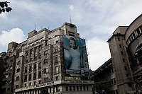 ROMANIA / Bucharest /22.06.2009 / Advertising hangs over historic pre-Communist buildings in the historic center of Bucharest. © Davin Ellicson / Anzenberger