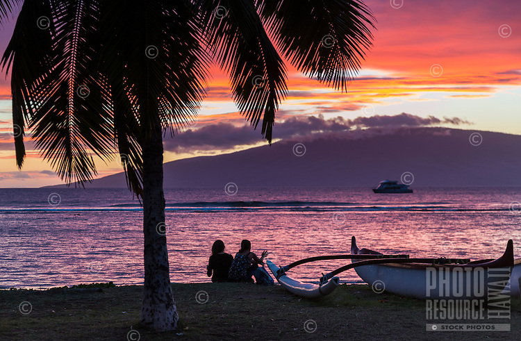 Tourists on a Maui beach watch the sun set behind Lana'i.