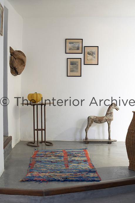 The hallway is furnished with a rag rug, a statue of a horse and a small metal table