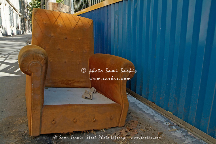 Old orange armchair is left abandoned in a city street.