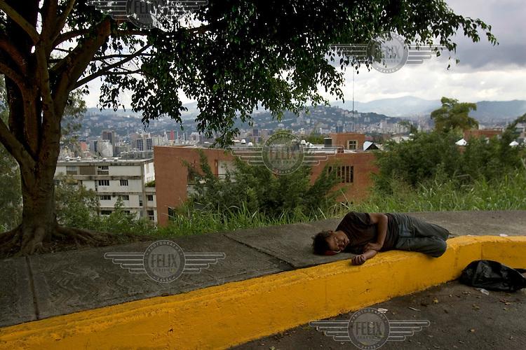 A homeless man asleep on a street corner on a hillside overlooking the city.