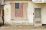 U.S. Flag hangin over window at a road-side house