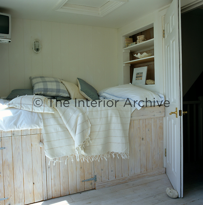 In this cosy bedroom the cabin-style bed is set on top of cupboards to save valuable space