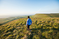 SIngle hiker near ridge on Twmpa with Hay Bluff in background, Black Mountain, Brecon Beacons national park, Wales