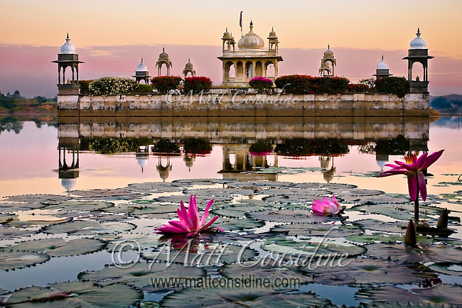 Early morning light illuminates a lake temple with lilies floating in the foreground.<br /> (Photo by Matt Considine - Images of Asia Collection)
