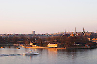An evening view over Stockholm Strom Strommen with an old style passenger ferry boat Djurgarden on the water in front of from left to right Skeppsholmen Kastellholmen and Djurgarden islands Stockholm, Sweden, Sverige, Europe