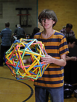 Origami folder and designer, Aaron Pfitzenmaier, Texas, USA holding one of his colorful modular creations at the OrigamiUSA 2013 Convention in New York.