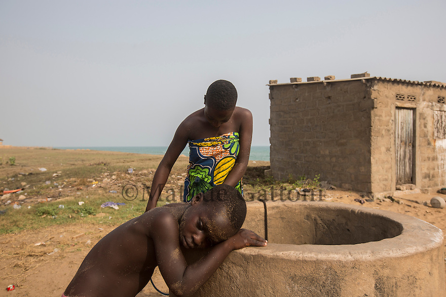 Togo - Agbavi - Villagers collecting water from a well that was contaminated by ocean water and therefore not safe to drink anymore.<br /> The village of Agbavi is one of the coastal erosion hotspots in Togo. Dozens of houses have already been lost, forcing the local population to relocate several times. Although coastal erosion has affected this coastline since the 60s, the phenomenon has increased massively after 2012 due to climate change and the enlargement of a nearby deep-sea port.