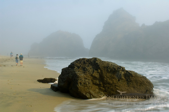 People walking on sand next to coastal rocks in fog at Pfeiffer Beach, Big Sur Coast, Monterey County, California