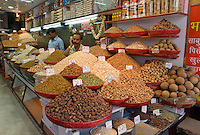 INDIAN MERCHANTS sell spices and dried fruit in the SPICE MARKET of CHANDNI CHOWK OLD DELHI - INDIA