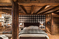 Black and white plaid fabric lines one wall of the master bedroom, while a white, painted mirror framed with antlers reflects  light around the wood clad walls and low beamed ceiling