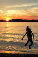 Girl leaping into the air above the setting sun, Sunset Beach, Washington Park, Anacortes, Skagit County, Washington
