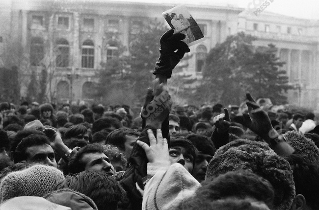 Romanian revolution, protestors hold up a photo of Nicolae Ceausescu and his wife in the days after the dictator fled Bucharest, Romania, December 1989