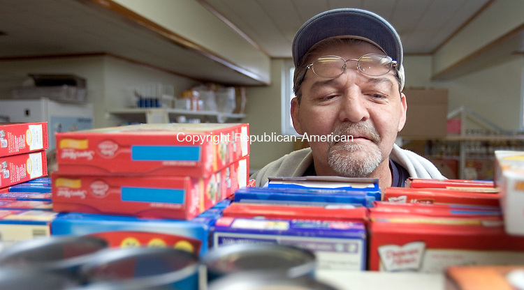 TERRYVILLE, CT. 26 November 2012-112612SV03-Jeff Tubbs of Plymouth looks for a cake mix while picking up food at the Plymouth Community Food Pantry in Plymouth Monday. The pantry handed out 150 turkey dinners with all the trimmings for Thanksgiving and is seeking donations for Christmas baskets. They will need to give out more they 150 baskets for the up coming holiday. Donations can be dropped off at the pantry of the volunteer ambulance..Steven Valenti Republican-American