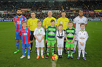 Children mascots with match officials including referee Mike Dean (C) and team captains Mile Jedinak of Crystal Palace (L) and Ashley Williams of Swansea (R) before the Barclays Premier League match between Swansea City and Crystal Palace at the Liberty Stadium, Swansea on February 06 2016