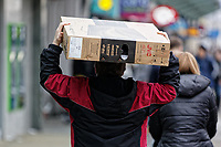 A last minute Christmas shopper carries a flat screen tv in Oxford Street, Swansea, Wales, UK. Monday 24 December 2018