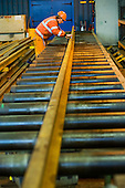 A worker in the Points and Crossings Shed of London Underground's  Lillie Road Depot prepares to bend a replacement rail to match a curve in the track.  The depot produces replacement track for the tube network and offers a same day service for 'urgencies and emergencies'.  The depot is now run by London Underground following the collapse of PPP contractor Metronet in 2007.