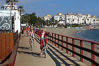 Cyclists on boardwalk between Puerto Banus & San Pedro de Alcantara. Puerto Banus is in the background. November 2015. 201511121799<br />
