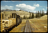 Train hauling flat cars with lumber.<br /> D&amp;RGW