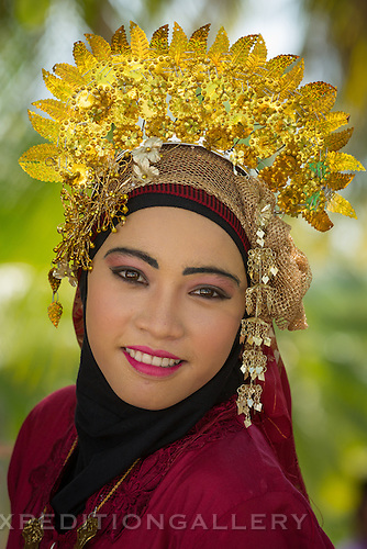 Smiling woman in festive traditional dress and ornaments as part of a local dance performance in the Natuna archipelago, Riau Islands Province, Indonesia. [NO MODEL RELEASE]