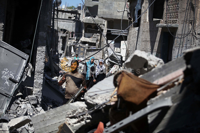Palestinians inspect the rubble of their houses during a 72-hour ceasefire observed in the Gaza Strip on August 11, 2014 in the northern Beit Hanun district of the Gaza Strip. Almost 12 hours into the truce, the skies over Gaza remained calm, with no reports of violations on any side and signs of life emerging on the streets of the war-torn coastal enclave which is home to 1.8 million Palestinians. Photo by Ashraf Amra