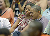 United States President Barack Obama gives first lady Michelle Obama a hug as they and their daughters Malia Obama and Sasha Obama attend the Hawaiian Airlines Diamond Head Classic men's basketball game between the Oregon State Beavers and the University of Akron Zips at the University of Hawaii at Manoa Stan Sheriff Center, Sunday, December 22, 2013. The first lady's brother, Craig Robinson, is the Oregon State University Men's Head Basketball Coach.  <br /> Credit: Cory Lum / Pool via CNP