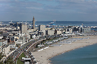 Beach and city of Le Havre, seen from Sainte Adresse, Seine-Maritime, Normandy, France. In the centre is the tower of the Eglise Saint-Joseph or St Joseph's Church, built 1951-58 as a memorial to the 5000 citizens of the town who died during the Second World War, designed by Auguste Perret, 1874-1954, and Raymond Audigier. Either side are the apartment blocks at Porte Oceane, completed 1956, also designed by Perret, with the docks of the port behind. Perret led the reconstruction of Le Havre in the 1950s, after the town was completely destroyed in WWII. The centre of Le Havre is listed as a UNESCO World Heritage Site. Picture by Manuel Cohen