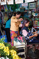 Myanmar, Burma.  Mandalay.  Hairdresser Dying Customer's Hair in Beauty Shop.