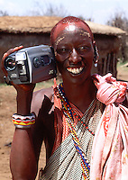 Portrait of a smiling Masai warrior in traditional attireholding a video camera. Kenya.